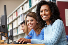 Étudiants travaillant sur des ordinateurs dans la bibliothèque Photos stock