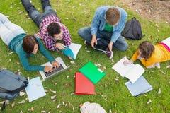Étudiants universitaires à l'aide de l'ordinateur portable tout en faisant le travail dans le parc Photographie stock libre de droits