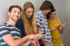 Étudiants universitaires à l'aide des téléphones portables Photographie stock libre de droits
