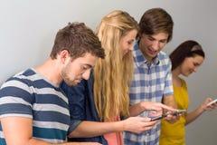 Étudiants universitaires à l'aide des téléphones portables Image stock