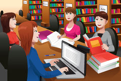 Étudiants universitaires étudiant dans une bibliothèque Photo libre de droits