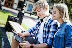 Étudiants universitaires amicaux souriant et employant le touchpad dehors images libres de droits