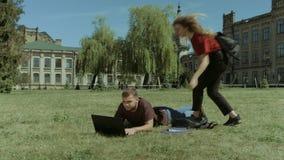 Étudiants universitaires appréciant des loisirs sur la pelouse de campus banque de vidéos