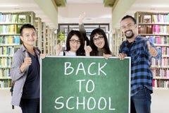 Étudiants universitaires avec de nouveau au mot d'école Photographie stock libre de droits