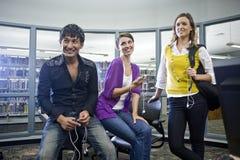 Étudiants universitaires avec des joueurs de musique dans la bibliothèque images libres de droits