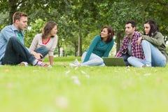 Étudiants universitaires avec l'ordinateur portable se reposant en parc Photographie stock