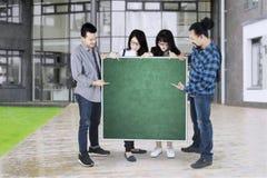 Étudiants universitaires avec le tableau vide Photographie stock