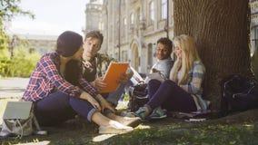 Étudiants universitaires ayant la discussion sous l'arbre sur le campus, se préparant aux examens Photographie stock libre de droits