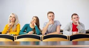 Étudiants universitaires de sourire réfléchis dans la salle de classe Photo libre de droits