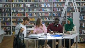 Étudiants universitaires ethniques multi se réunissant dans la bibliothèque banque de vidéos