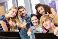 Étudiants universitaires faisant des gestes des pouces  Image libre de droits