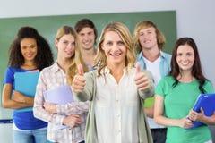 Étudiants universitaires faisant des gestes des pouces  Photos stock