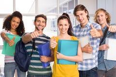 Étudiants universitaires faisant des gestes des pouces  Photographie stock