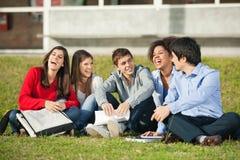 Étudiants universitaires gais s'asseyant sur l'herbe à Photographie stock