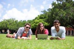Étudiants universitaires heureux à l'aide de l'ordinateur Images libres de droits