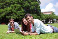 Étudiants universitaires heureux à l'aide de l'ordinateur Photographie stock