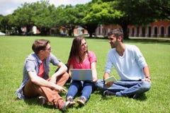 Étudiants universitaires heureux à l'aide de l'ordinateur Photos stock