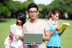 Étudiants universitaires heureux à l'aide de l'ordinateur Photos libres de droits