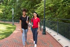 2 étudiants universitaires marchant sur le campus Photos stock