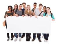 Étudiants universitaires montrant le panneau d'affichage vide Photo stock