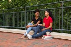 2 étudiants universitaires parlant sur le campus Image libre de droits