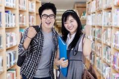 Étudiants universitaires réussis dans la bibliothèque Images stock