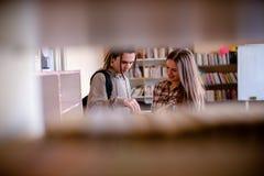 Étudiants universitaires recherchant des examens ensemble photos stock