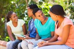 Étudiants universitaires s'asseyant dehors Photo stock