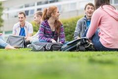 Étudiants universitaires s'asseyant en parc Images stock
