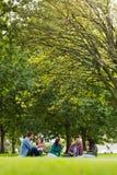 Étudiants universitaires s'asseyant sur l'herbe en parc Images libres de droits