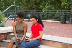 2 étudiants universitaires sur le campus regardant leurs téléphones portables Image stock