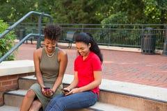 2 étudiants universitaires sur le campus regardant leurs téléphones portables Images stock