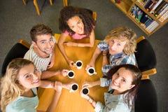 Étudiants universitaires tenant des tasses de café sur la table Image libre de droits