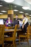Étudiants universitaires traînant par des ordinateurs de bibliothèque Photographie stock libre de droits