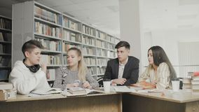 Étudiants universitaires travaillant ensemble la préparation aux examens tout en se reposant à la table à la bibliothèque univers banque de vidéos