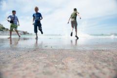 Évasion de trois enfants des vagues de augmentation Image stock