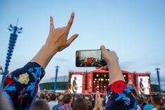 Éventez dans la foule utilisant le téléphone intelligent et prendre une photo de bande préférée de musicien au festival de musiqu Images libres de droits