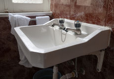 Évier blanc classique avec de vieilles tuiles dans une salle de bains avec des serviettes Images stock