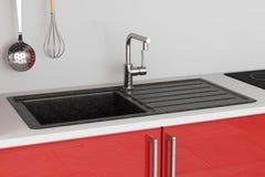 Évier de cuisine moderne de granit avec le robinet d'eau d'acier inoxydable, construction de robinet dans les meubles rouges de c photographie stock libre de droits