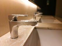 Évier de salle de bains de nettoyage dans les toilettes publiques images libres de droits