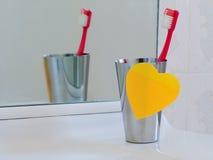 Évier de salle de bains avec la note et la brosse à dents collantes de coeur Aimez votre t Photographie stock libre de droits