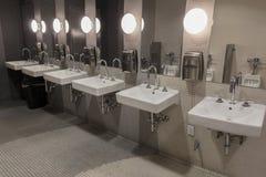 Éviers dans les toilettes publiques images stock