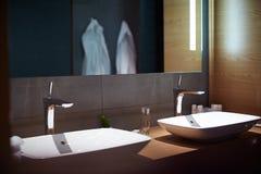 Éviers de salle de bains, manteaux blancs Image stock
