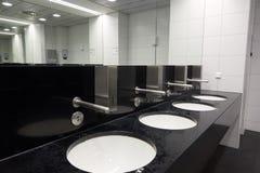 Éviers modernes dans la toilette publique avec le système de commutation automatique de l'eau Photo libre de droits