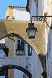 ÉVORA, PORTUGAL: Close-up em lâmpadas e em arcos de rua em uma rua estreita imagem de stock royalty free