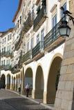 ÉVORA, PORTUGAL - 8 DE OUTUBRO DE 2016: As fachadas e as arcadas típicas da casa em Giraldo Square com um dragão deram forma à lâ fotografia de stock