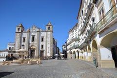 ÉVORA, PORTUGAL - 8 DE OUTUBRO DE 2016: Giraldo Square com Santo Antao Church e fachadas e arcadas típicas da casa fotos de stock royalty free