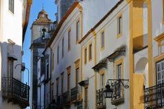 ÉVORA, PORTUGAL: rua estreita típica com casas brancas e a igreja do Sao Mamede no fundo fotos de stock
