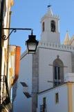 ÉVORA, PORTUGAL: Uma lâmpada de rua com Sao Francisco Church no fundo imagens de stock royalty free