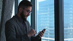 Éxito empresarial y logro - celebración que anima del hombre de negocios feliz en el teléfono celular Profesional urbano joven almacen de metraje de vídeo
